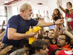 Ex-President Lula is carried by supporters before handing himself over to the police