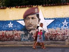 Women walk past a mural of Hugo Chávez on January 31, 2019 in Caracas, Venezuela. (Edilzon Gamez / Getty)