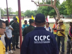 Local police officials and soldiers address indigenous citizens of the Sierra de Perija region of Venezuela