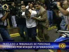 One of the eleven arrested suspects in the synagogue attack being transported to court. (Globovision)