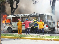 Fire fighters extinguish a UCV bus burned by assailants during  the opposition march last May 20th