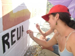 Lisbeida Rangel helping to paint a community noticeboard (Tamara Pearson)