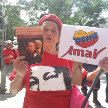 A Chavista supporter holds up a political pamphlet (Ricardo Vaz)