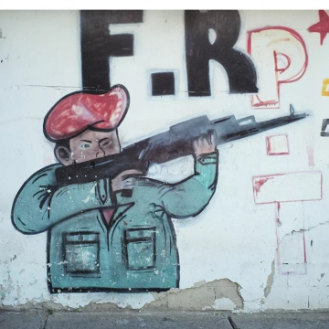 A Caracas mural depicts former president Hugo Chavez with a gun. (Ronald Pizzoferrato)