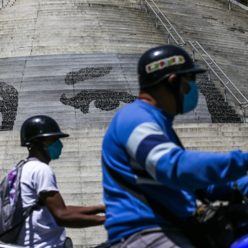 Motorbike users, which is the common means of transport for Venezuela's poorer sectors, have also had to adapt to the measures by wearing facemasks and limiting movement. (Cristian Hernández / AFP)