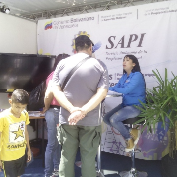Workers of Venezuela's Autonomous Service of Intellectual Property talk to visitors to the FILVEN 2018