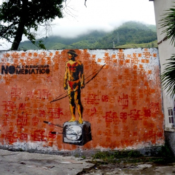 "In the struggle to resist modern-day forms of neocolonialism, including domination via thought/media, the Communicational Guerrilla produced this 10-foot high mural that reads, ""No to Media Colonialism."""
