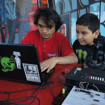 One of the many computer tech volunteers at FLISOL demonstrates how to use Linux-based music mixing and editing programs to a curious young Venezuelan (Luigino Bracci).