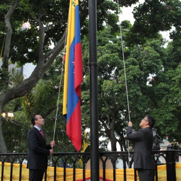 Minister for justice Tarek El Aissami (left) and vice-president of the country, Elias Jaua, raise the national flag (CdO)