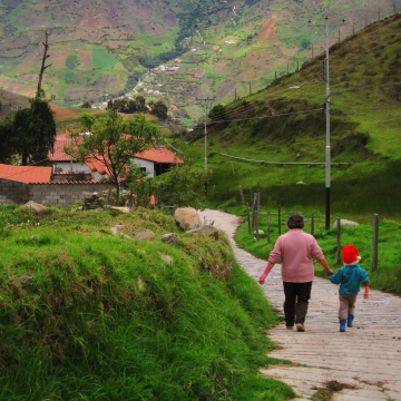 A Venezuelan woman and child walk through the small rural village of Gabidia, in the Venezuelan paramo. Note the child's head is kept warm by a small red Christmas cap (Mason London).