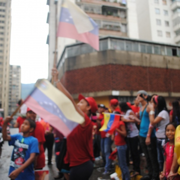 Chavistas react to a woman holding a Capriles poster in front of her window (whilst covering her face!) (Rachael Boothroyd/Venezuelanalysis.com)