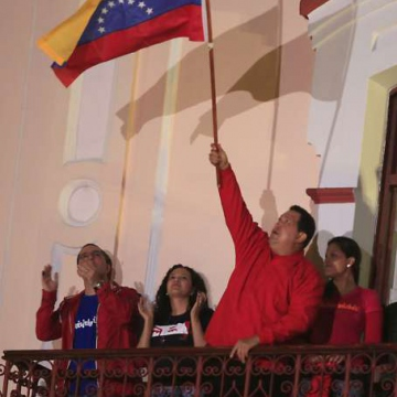 Chavez waves the Venezuelan flag while addressing the crowd from the Balcony of the People (AVN)