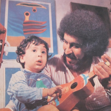 """Ali Primera with one of his four sons and the Venezuelan four-string guitar known as the """"cuatro""""."""