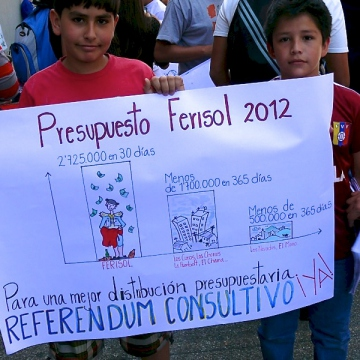 Children with a placard illustrating the large amount of public spending on the Carnaval in Merida this year, compared to spending on communities (Fermin E Osorio)
