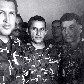 "After the massacre of up to 3000 Caracas citizens by the Perez administration in 1989, Chavez (left) and the MBR-200 began to seriously consider overthrowing the government. Chavez saw the austerity measures that led to widespread protests and the subsequent government crackdown (now known as El Caracazo) as products of a corrupt, undemocratic system. On February 4, 1992, Chavez launched his coup, which was quickly suppressed. After becoming isolated from his network of supporters, Chavez and a small group of fellow soldiers were surrounded by government forces in the Military Museum in Caracas. Chavez surrendered, but on the condition that he be permitted to address the nation on television. He famously conceded defeat with the words, ""por ahora"" (for now). Overnight, he became a national hero. (Reuters/Corbis)"