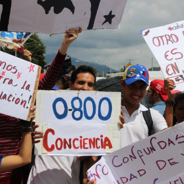"""Protest in Merida against consumerism. Placards (from left to right) """"fight against speculation"""", """"0-800 Consciousness"""" (a reference to government 0800 numbers that receive complaints about businesses and economic sabotage), """"Another beta version is possible"""" (Ryan Mallett-Outtrim/Venezuelanalysis)"""