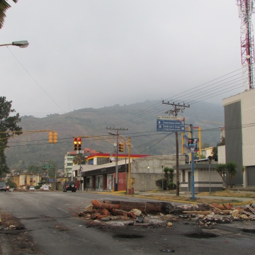 The barricades intensified however, with militants using burning rubbish, trees, torn up street lamps, bus stops, corrugated iron, barbed wire, and anything else to try and permanently block roads. This small barricade made from tree trunks was partially removed to allow one lane traffic. Others can be seen in the background.