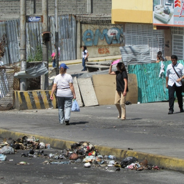 Local residents pass through a gap on the side of the barricade, and walk the rest of the way home.