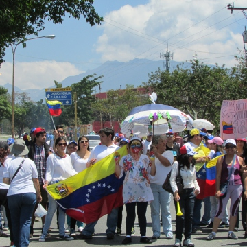 """Participants in the march. The women with the painted face has the words """"peace"""" """"love"""" and """"freedom"""" painted on her hands and hat. Another has a banner reading """"no more violence"""". One participant, a local opposition councillor, blamed authorities and pro-government groups for the violence, saying that they had attacked opposition activists. She also said the barricades were for """"self-defence"""" and that any violence on them was caused by """"infiltrators"""".   It is worth noting that the only two deaths from the unrest to occur in Mérida were related to the barricades. One occured when a woman, Delia Elena Lobo (41), died after her motorbike crashed into the barbed wire of a street barricade. The second was when a pro-government activist, Gisela Rubilar Figueroa (47), was shot by assailants while she tried to clear a barricade that was blocking access to her community."""