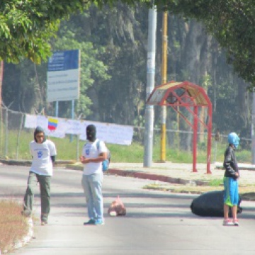"""Taken on 7 February, this photo shows a few activists at the beginning of the hard-line opposition's road blocks in Mérida. The actions began shortly after radical opposition leaders Leopoldo Lopez and Maria Corina Machado called on supporters to """"light up the streets of Venezuela with struggle"""" in a strategy called """"The Exit"""".   These militants used a stolen truck and burning tyres to block the road outside of the law faculty of the University of the Andes (ULA), and threw stones at anyone who came close. No banners were shown explaining the reasons for their actions. The tactic of road blocks, or guarimbas, were also being used in the city of San Cristobal in the neighboring state of Tachira, where the protests and unrest began, ostensibly over the issue of insecurity. A few days after this photo was taken, the first riots occurred in Mérida, and on 12 February the opposition's unrest went national after deadly clashes took place in Caracas. The ULA in Mérida has since been closed due to the disturbances in the city."""