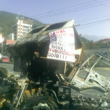 """The burnt remains of the truck. The message hanging from it says, """"What Normality? Fear? Shortages? Dictatorship? Ruin? Cubanization? Hate!"""". (Tamara Pearson, Veneuelanalysis.com)"""