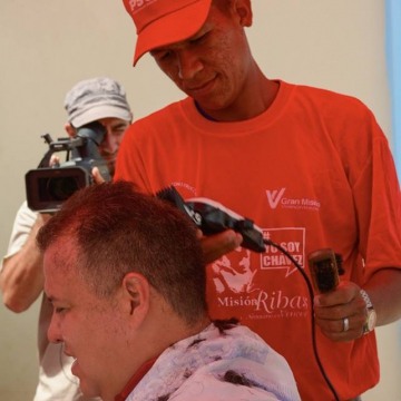 Communes minister Iturriza receives a community haircut during a day of volunteer work in La Trinidad, Apure