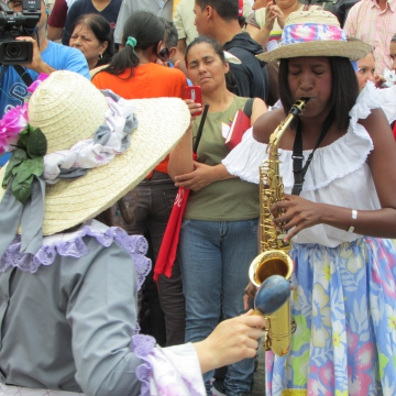 A woman plays the saxophone in another traditional dance.