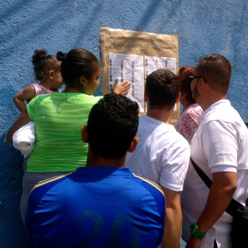 Residents check out the list of candidates. Nominees included both Chavistas and opposition supporters. (Rachael Boothroyd Rojas - Venezuelanalysis)
