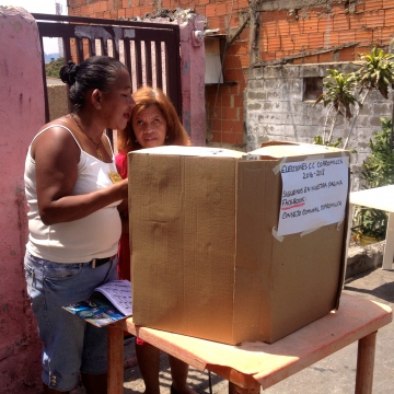A member of the electoral committee helps a member of the community with disabilities to vote (Rachael Boothroyd Rojas - Venezuelanalysis)