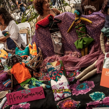 "A stall from collective ""Afrohermanas"" (Afro-sisters), who make artisan goods out of fabric. Their products include rag dolls for Venezuelan children which reflect their own skin colour, as well as breastfeeding pillows for new mothers (Afroo Raiz Afroo Indigena)."