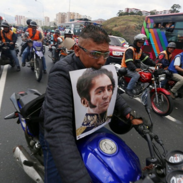 Motorcyclist clutches poster of Venezuela's independence hero Simon Bolivar. The image is the result of a scientific reconstruction of Bolivar's likeness, revealing the liberator's mixed African and European heritage in contrast to previous whitened portrayals. Motorcyclists, who themselves mainly hail from the country's black and brown barrios, have long been among the Bolivarian Revolution's strongest supporters.