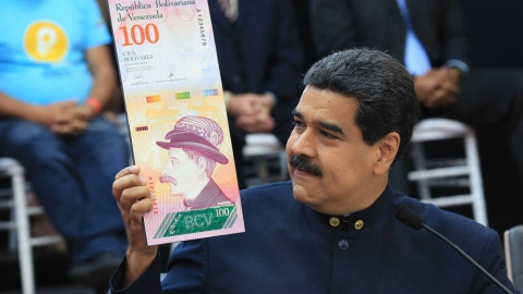 Venezuelan President Nicolas Maduro shows off the new 100 Sovereign Bolivar bill