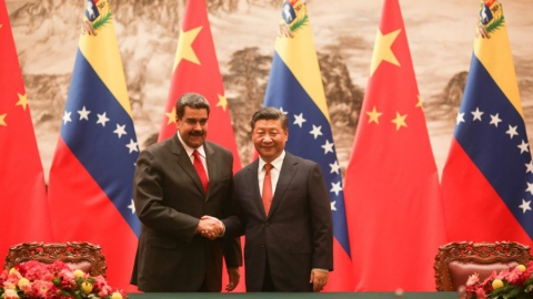 Venezuelan President Maduro (L) shakes the hand of Chinese President Xi Jinping during his state visit to China