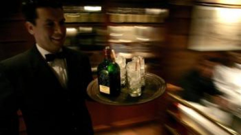 A waiter carries Scotch whisky to customers at a bar in Caracas (AP/Fernando Llano)