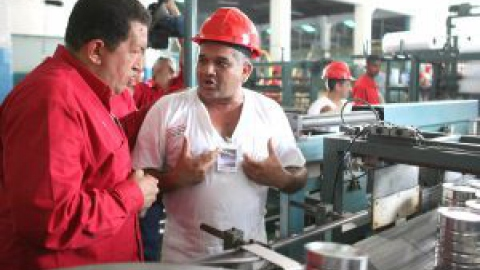 Venezuelan President Hugo Chavez talks to a worker during the inauguration of a milk processing plant on Sunday. (Prensa Presidencial)