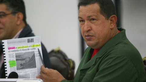 President Hugo Chavez holds up a news article about the Guri dam
