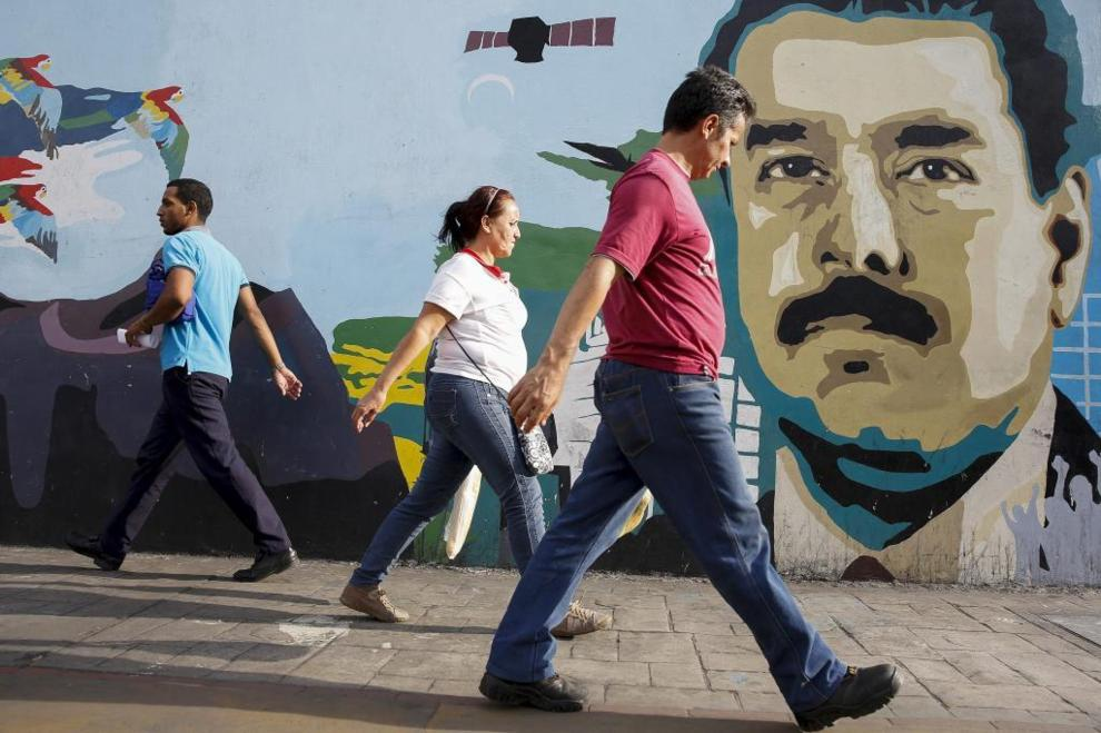 People walk past a campaign mural of Venezuela's President Nicolas Maduro in Caracas. (REUTERS)