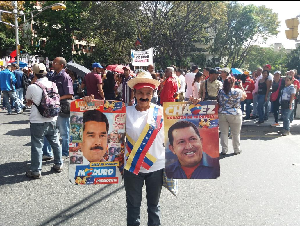 A government supporter holds up Maduro and Chavez campaign posters (Ricardo Vaz)