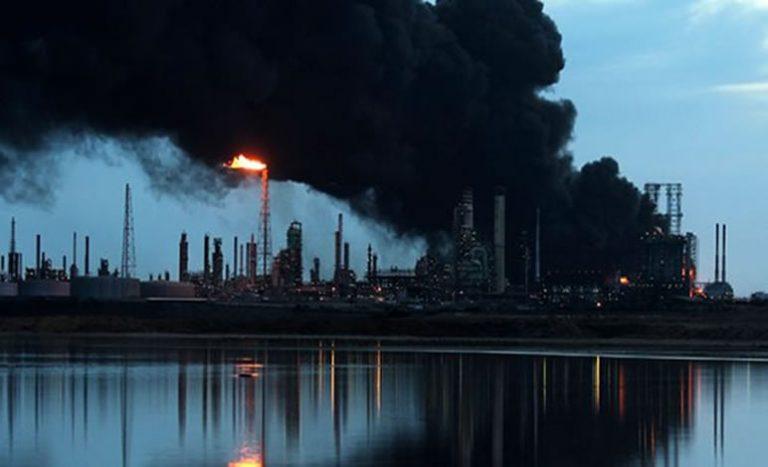 An oil refinery pumps out smoke. (Lacomunidadpetrolera.com)