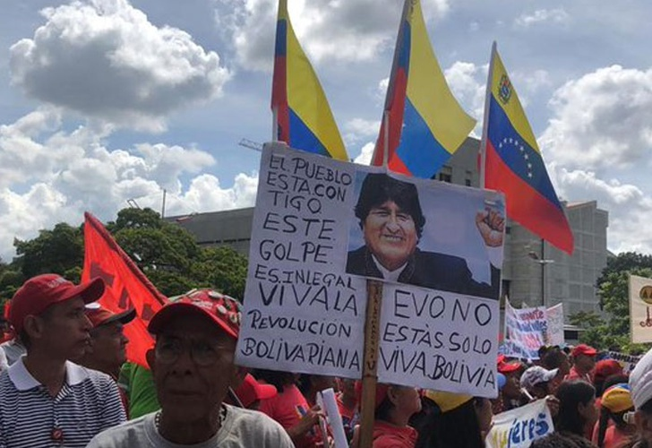 "A man holds a placard at the Caracas march which reads ""The people are with you. This coup is illegal. Long live the Bolivarian Revolution. Evo you are not alone. Long live Bolivia."" (Reference)"