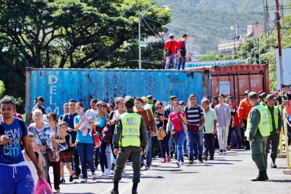 Citizens queue up to cross the reopened Colombo-Venezuelan border, avoiding containers which were used to block the crossing in February. (AFP)