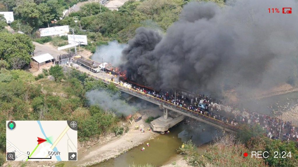 """A truck allegedly carrying """"aid"""" from USAID is set on fire halfway across the Simon Bolivar international bridge connecting Venezuela and Colombia February 23, 2019, The Venezuelan National Guard piquet can be observed in the top left of the image, and the multitude of protesters stemming from the Colombian side coming from the bottom right (Courtesy)"""