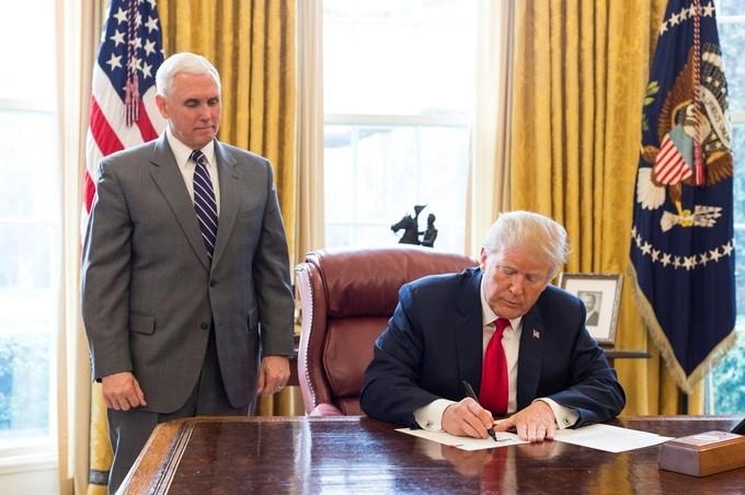 Donald Trump signs a document in the Oval Office. (Archive)
