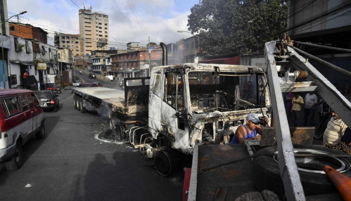 Clashes in Petare left several vehicles torched. (AFP)