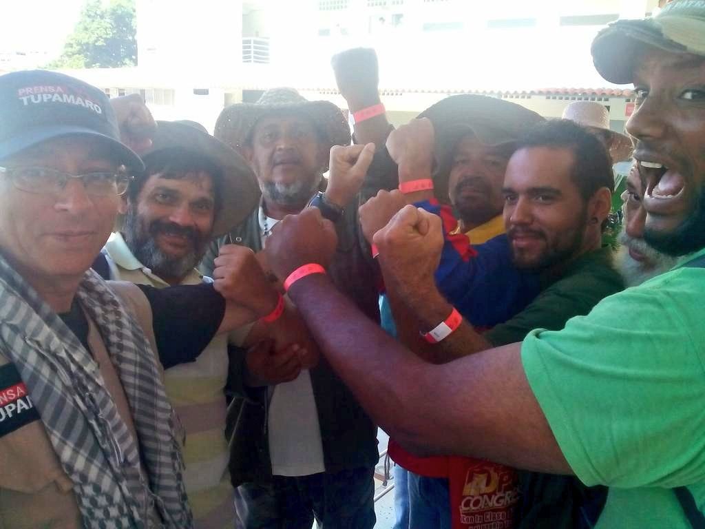 Farmers show their wristbands which allow them to enter the presidential palace with joy