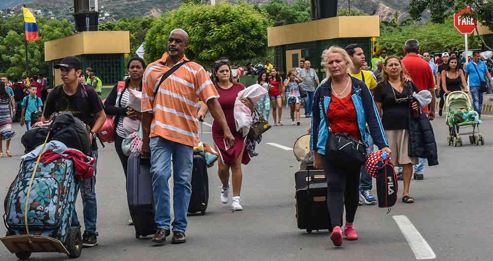 Venezuelans carry their belongings as they seek new destinations. (Semana)
