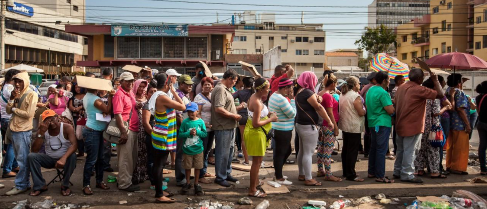 People cue up outside of a bank to get cash, Caracas, November 2019. With hyperinflation, getting cash for cash-only payments such as transportation became an ordeal for working-class Venezuelans. (AP)