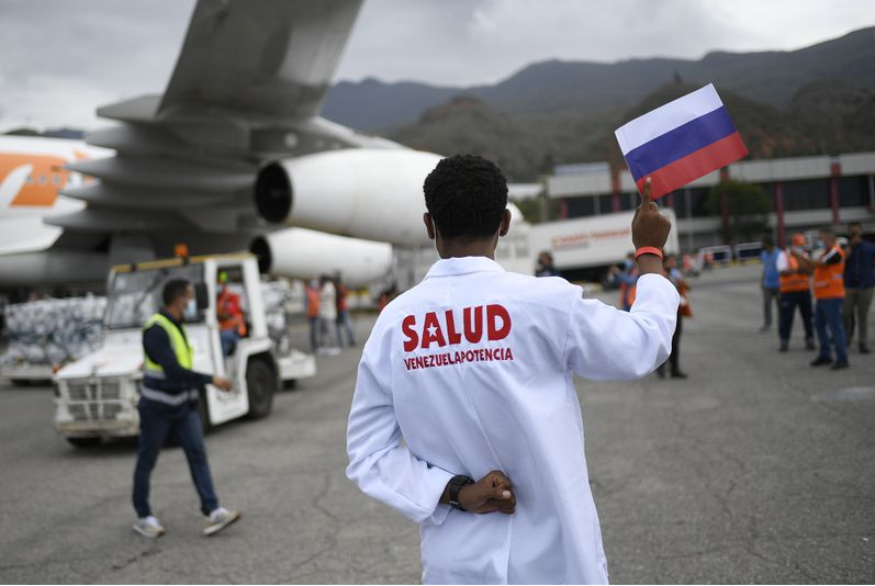 A Venezuelan healthcare worker waves a Russian flag to receive the Covid-19 vaccine in Caracas airport. (Matias Delacroix / AP)
