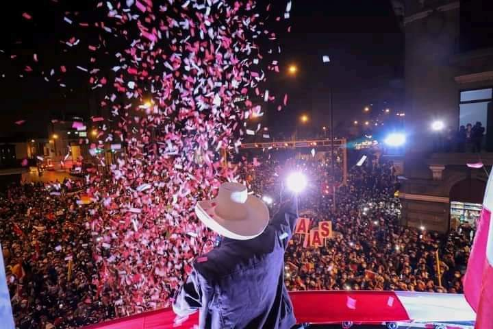 Pedro Castillo waves in front of a large crowd at night