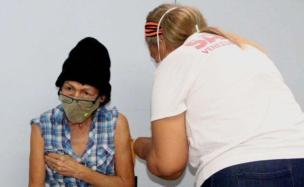 A health professional injects a senior woman